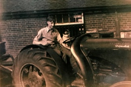 Colin Evered and his dog, Peggy, sitting on a tractor