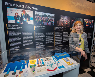 Vicky Hope-Walker standing next to the Bradford stories exhibition display at Cartwright Hall Art Gallery