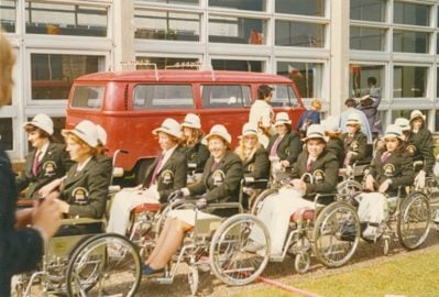 Women wheelchair athletes in 1972, with matching dark blazers and white hats, lining up.