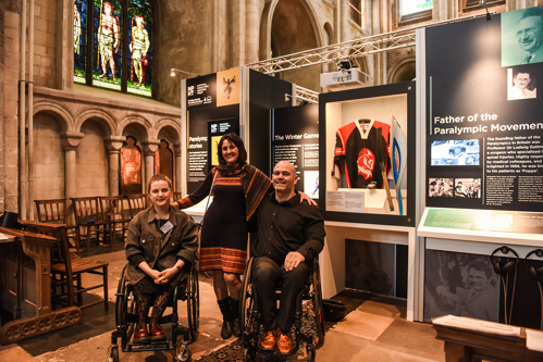 Ella Glendining, Anne Wight and Danny Nobbs in front of the exhibition display at Norwich Cathedral