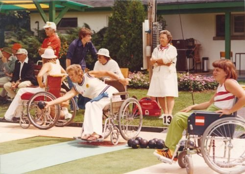 Margaret Maughan with other women wheelchair athletes playing bowls. Umpire to the back of them.