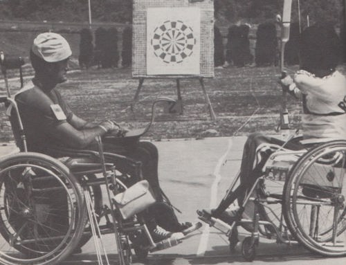 Black and white photo of two wheelchair participants playing Dartchery