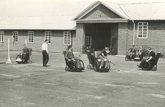 A group of people playing wheelchair hockey outside Stoke Mandeville in the 1940s