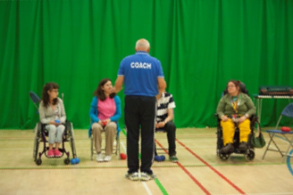 Roy McGee coaching a group of Boccia players