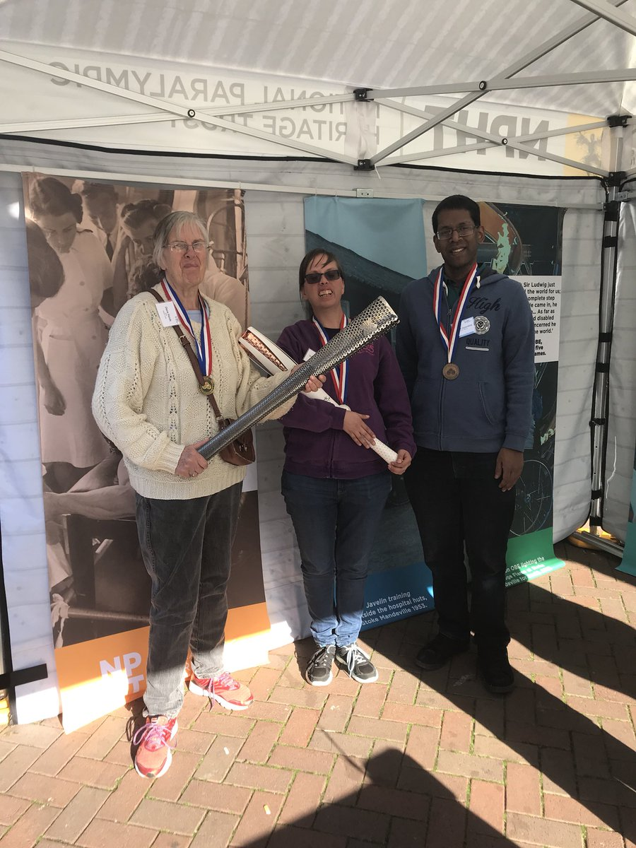 Three of the volunteers from I have a voice too standing in the pop-up museum holding Paralympic torches