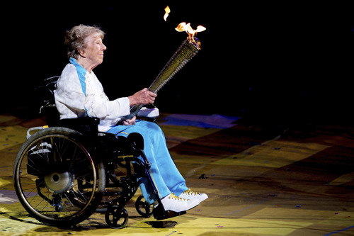 Margaret Maughan holding the lit Paralympic Torch at the London 2012 Paralympics opening ceremony