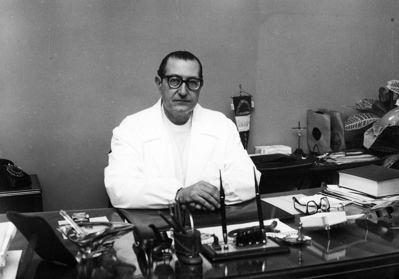 Black and white photo of Dr Antonio Maglio in Doctors white coat sat behind his desk
