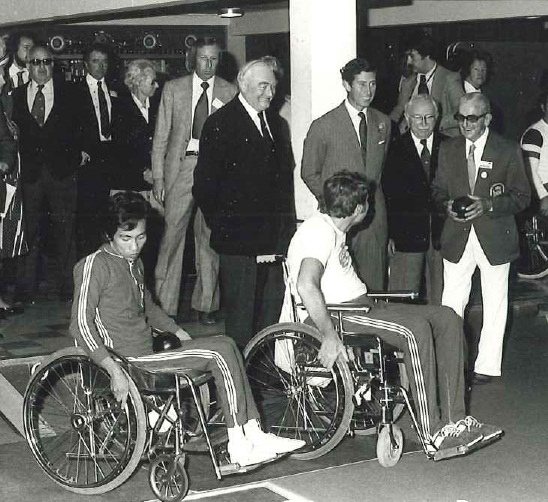 Prince Charles, Sir Ludwig Guttman and Jack Sutherland in the Indoor Bowls Centre at the 1973 International Games with two wheelchair bowlers and other officials behind them.