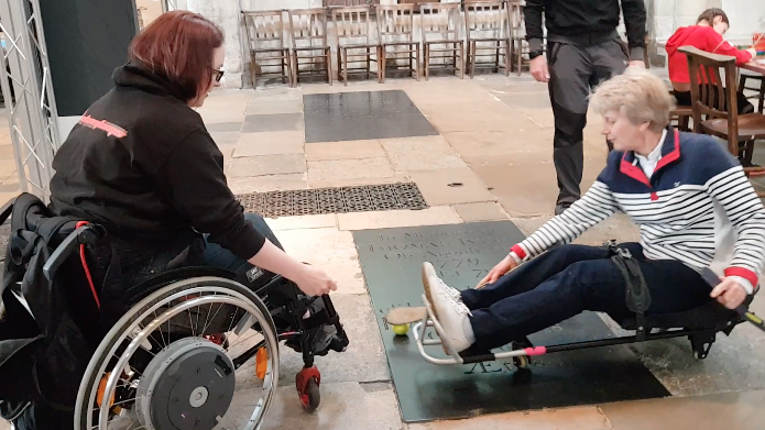 The Dean of Norwich Cathedral trying out Sledge Hockey with the help of Naomie Adie from the Peterborough Phantoms