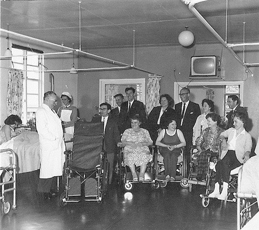 Professor Sir Ludwig Guttmann and the patients receiving a wheelchair