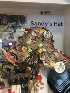 Sandys hat covered in badges from sporting events in the 1980s onwards in a display cabinet
