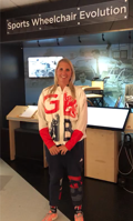 Stephanie Millward MBE in front of the Sports Wheelchair Evolution display at the National Paralympic Heritage Centre