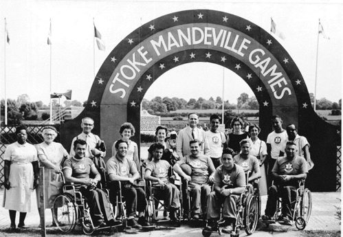 Wheelchair basketball team, nurses and doctors under the Stoke Mandeville Games archway in the 1960s