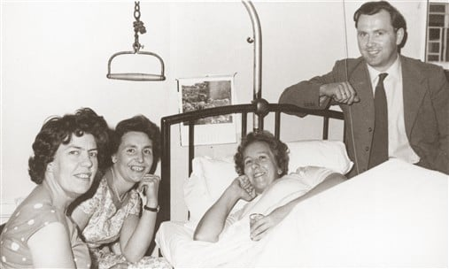 Margaret Maughan as a patient in a bed surrounded by family members