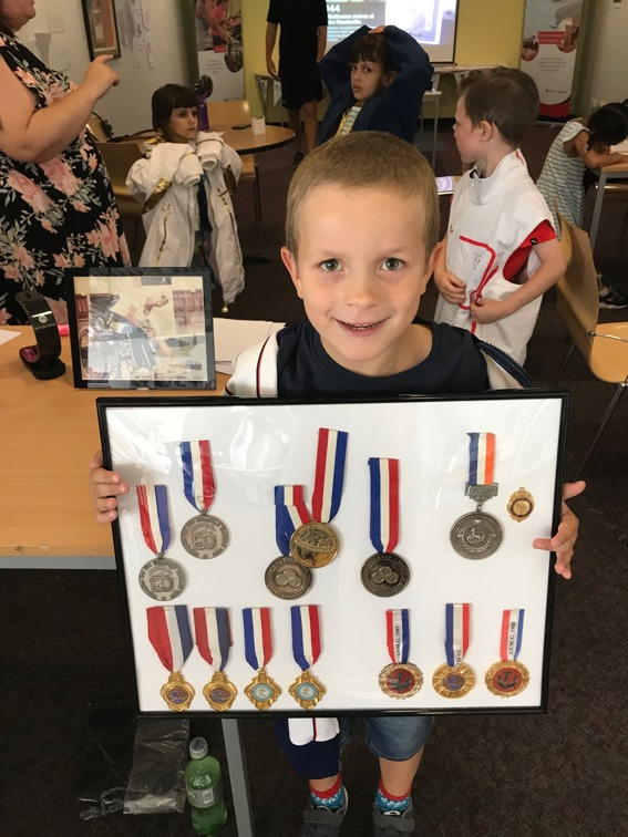 Child holding up Paralympic medals at the 70th anniversary activity week