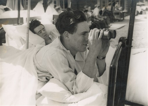 Two patients in beds outside watching sport through binoculars