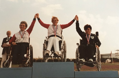 Angela Hendra with Yvonne and Rita on the podium with their medals at the Stoke Mandeville 1984 Paralympics