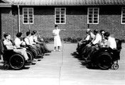 Physiotherapist and patients in wheelchairs outside with medicine balls