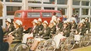 Women wheelchair athletes, with matching dark blazers and white hats, lining up.