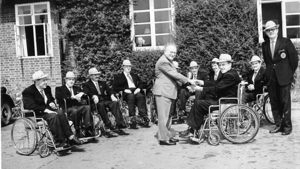 Professor Sir Ludwig Guttmann shaking hands with smartly dressed men in wheelchairs