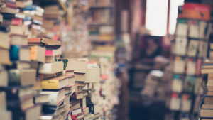Multiple, untidy stacks of books in a small space
