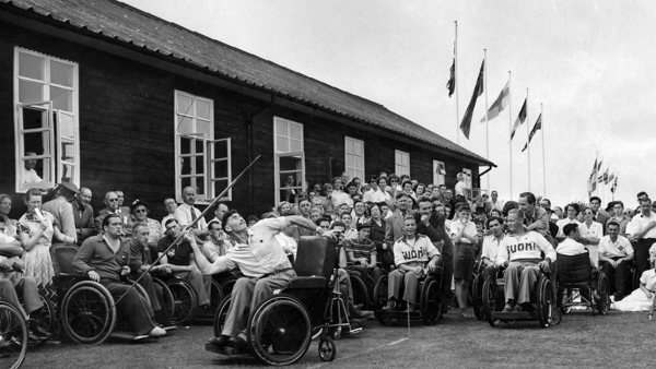 Black and white photo of men in wheelchairs competing in archery at an early Stoke Mandeville Games