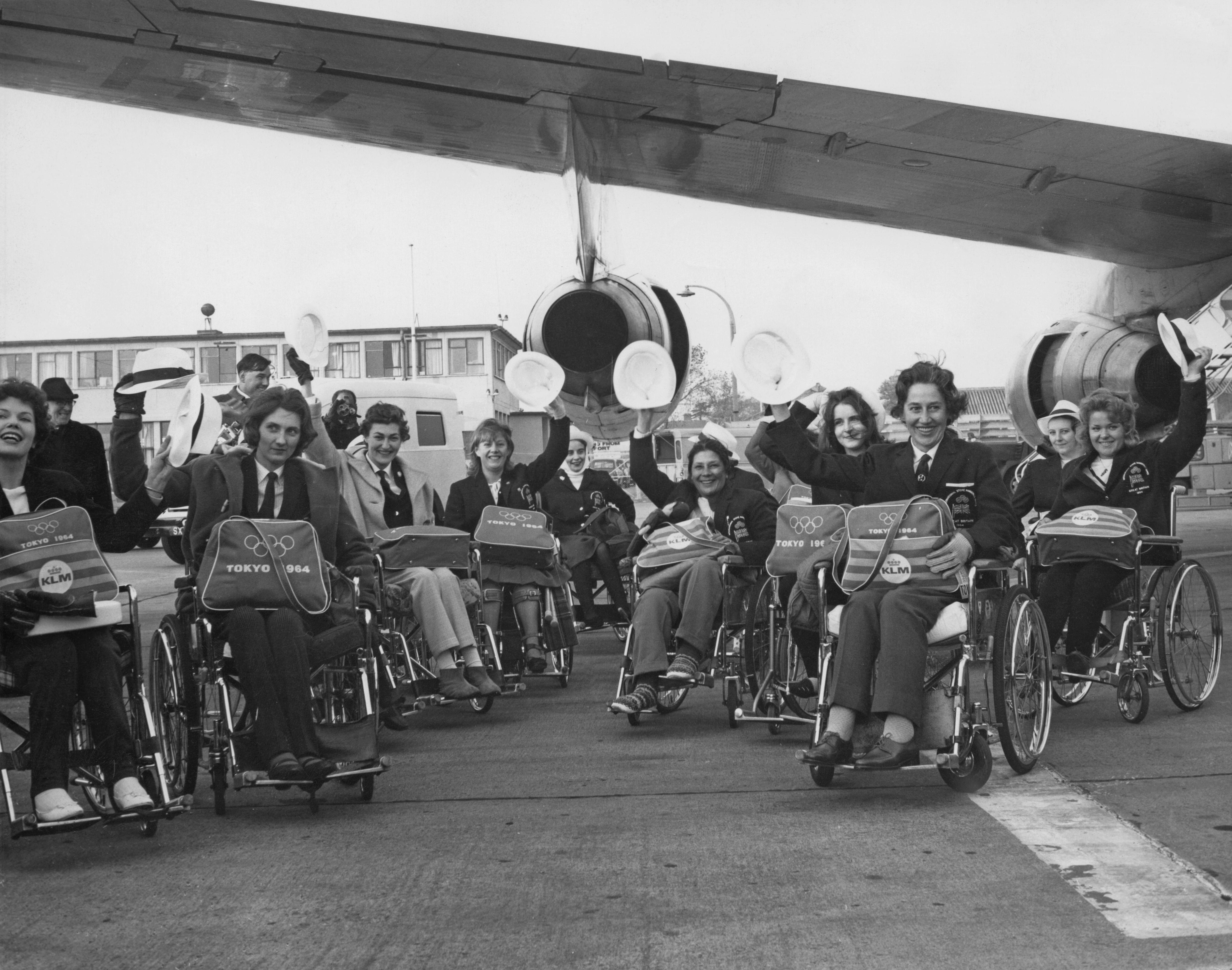 Black and white photo of Para-athletes in front of the plane on their way to the 1964 Tokyo Paralympic Games.